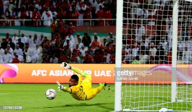 Oman's goalkeeper Ammar alRusheidi dives and misses the ball to give Uzbekistan the first goal of the match during the 2019 AFC Asian Cup group F...