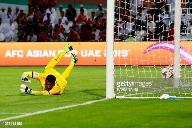 Oman's goalkeeper Ammar alRusheidi misses the ball to give Uzbekistan the first goal of the match during the 2019 AFC Asian Cup group F football...