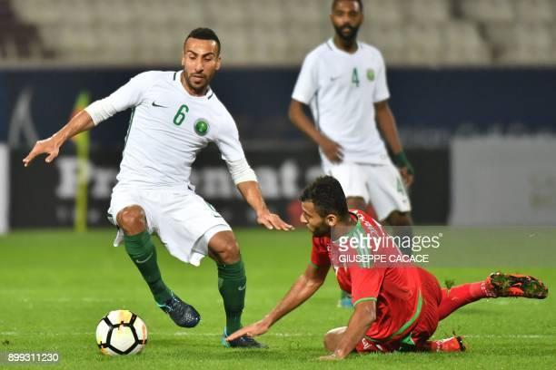 Oman's Raed Ibrahim Saleh vies for the ball against Saudi's Salman alMoasher during the 2017 Gulf Cup of Nations football match between Saudi Arbia...