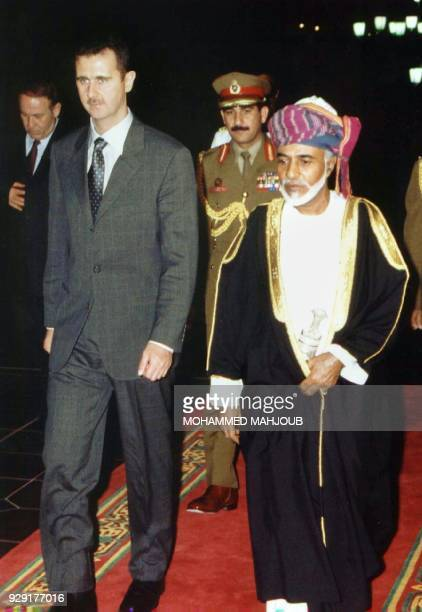 Oman's ruler Sultan Qaboos walks with Syrian President Bashar alAssad upon his arrival in Muscat 12 May 2001 The two leaders are expected to discuss...