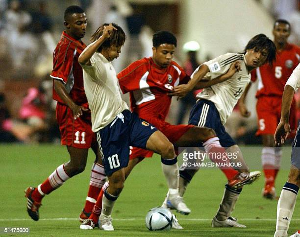 Oman's Yussef Shaaban and Hamdi Hubeis fight for the ball against Nakamura Shunsuke and Suzuki Takayuki of Japan during their World Cup 2006 Asian...
