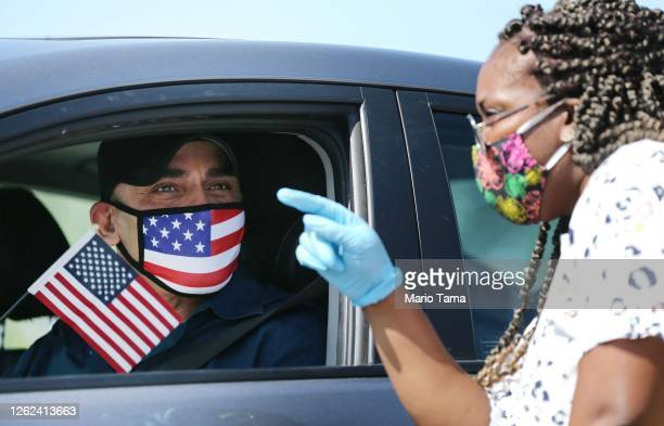 Omar Abdalla, originally from Palestine, holds an American flag after being sworn in as a new U.S. Citizen by an immigration service officer from his...