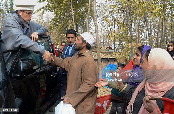Omar Abdullah Chief Minister of Jammu and Kashmir and president of the National Conference party and a contesting candidate shake hands with his...