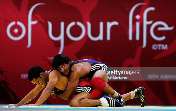 Omar Abdulqader of Qatar competes with Yogeshwar Dutt of India in the Men's Freestyle 60kg - Repechage at the 15th Asian Games Doha 2006 at the...