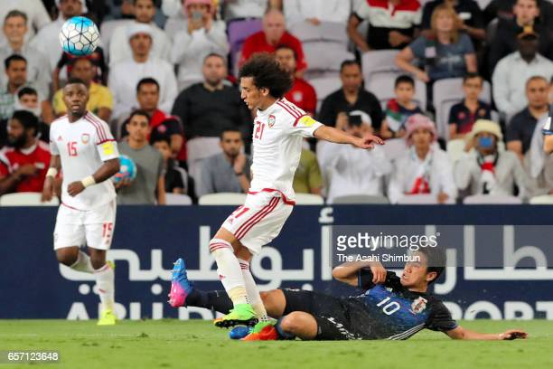 Omar Abdulrahman of the UAE is tackled by Shinji Kagawa of Japan during the FIFA 2018 World Cup qualifying match between United Arab Emirates and...