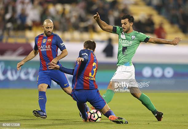 Omar al Soma of Al-Ahli Saudi FC tackled by Gerald Pique and Javier Mascherano of Barcelona during the Qatar Airways Cup match between FC Barcelona...