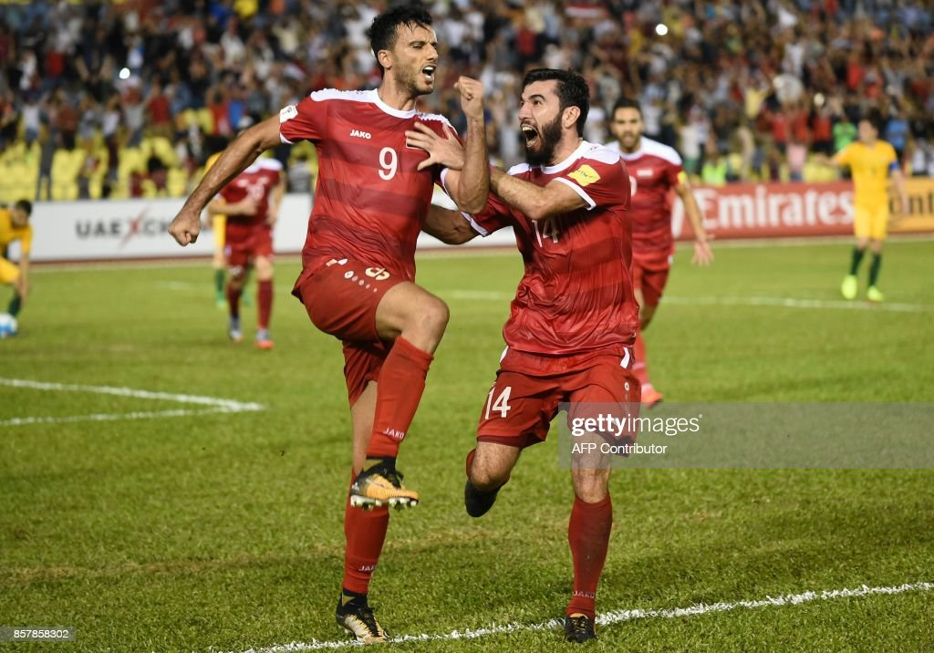 Omar Al Somah of Syria (L) celebrates a penalty goal with a teammate against Australia during the 2018 World Cup qualifying football match between Syria and Australia at the Hang Jebat Stadium in Malacca on October 5, 2017. /