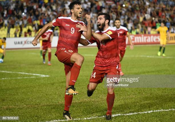 Omar Al Somah of Syria celebrates a penalty goal with a teammate against Australia during the 2018 World Cup qualifying football match between Syria...