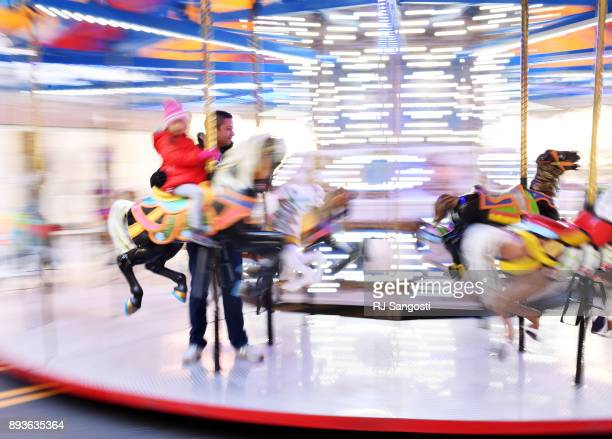 Omar Barajas and his daughter Sabrina on vacation from Texas ride the Denver Pavilions Holiday Carousel on December 15 2017 in Denver Colorado The...