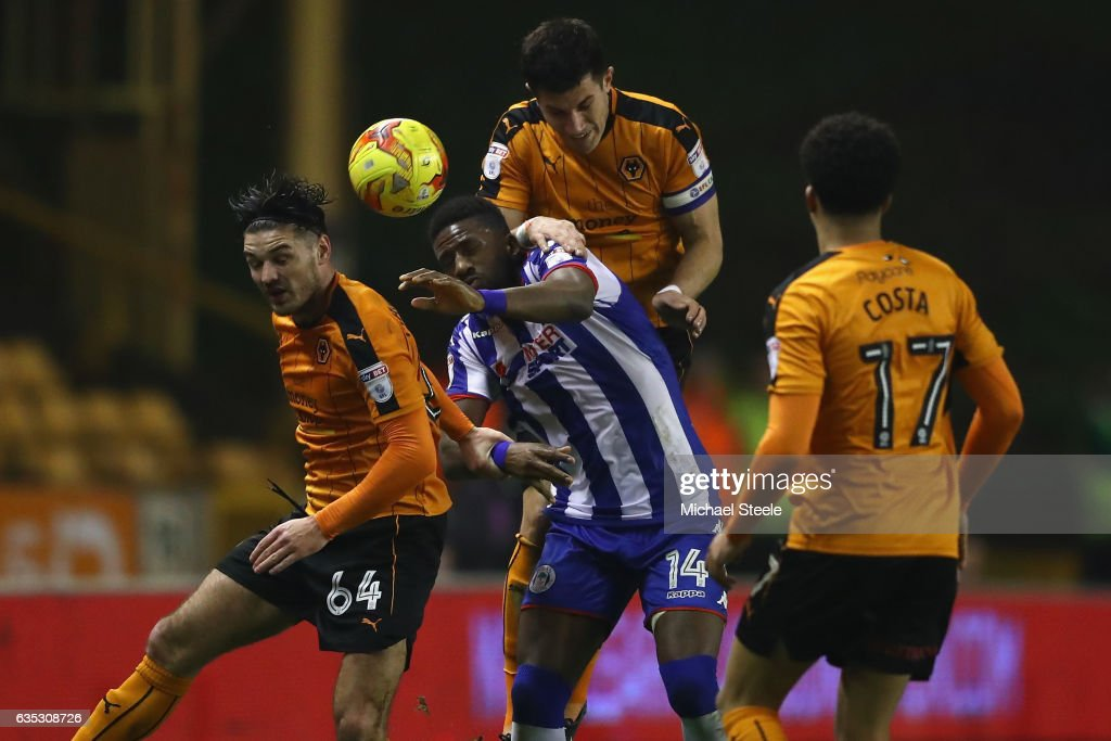 Omar Bogle of Wigan is crowded out by Danny Batth (C), Ben Marshall (L) and Helder Costa (R) of Wolverhampton during the Sky Bet Championship match between Wolverhampton Wanderers and Wigan Athletic at Molineux on February 14, 2017 in Wolverhampton, England.