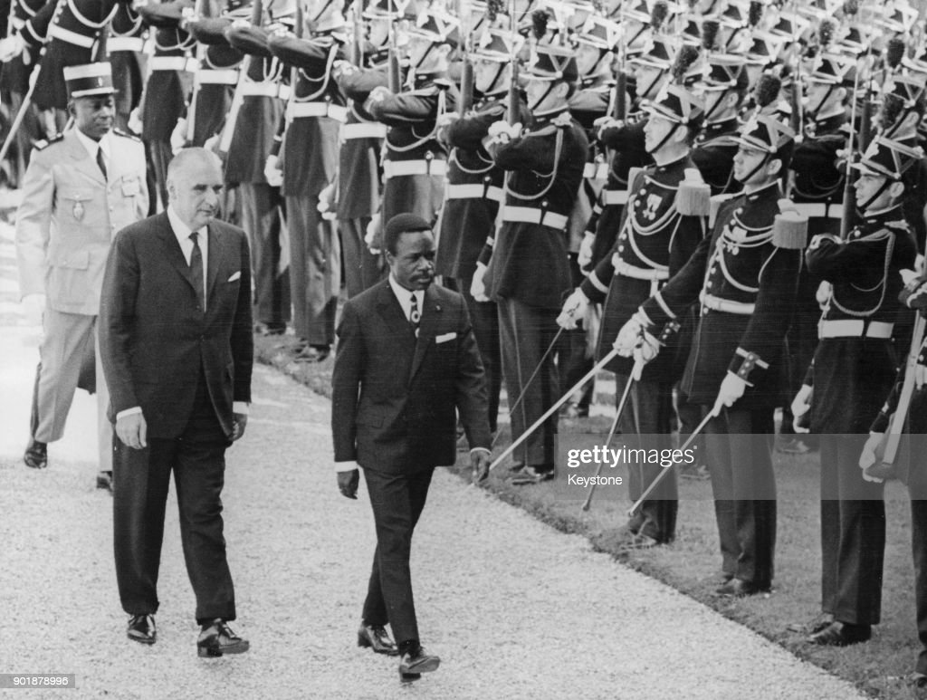 Omar Bongo (1935 - 2009), the President of Gabon, inspects a guard of honour of the French Republican Guard with French President Georges Pompidou (1911 - 1974, left), after arriving in Paris, France, 6th July 1970.