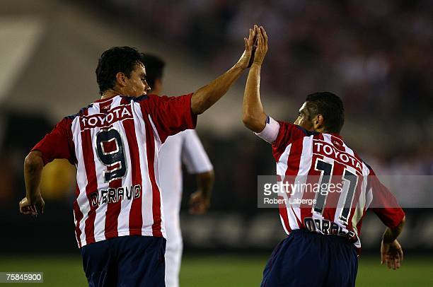 Omar Bravo and Ramon Morales of CD Chivas de Guadalajara celebrate after Bravo scored a goal in the second half against the Los Angeles Galaxy during...