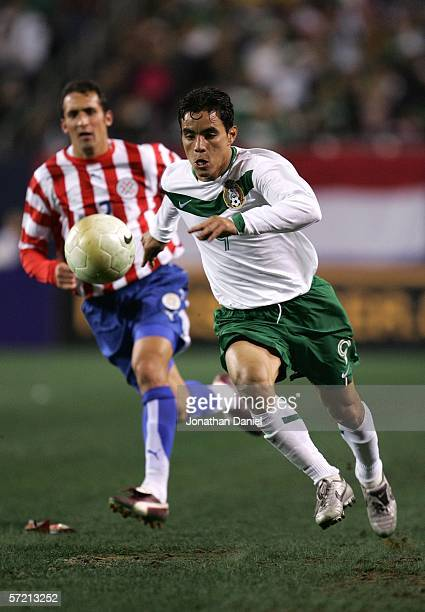 Omar Bravo of Mexico heads downfield as Ignacion Paniagua of Paraguay chases during a friendly match March 29 2006 at Soldier Field in Chicago...