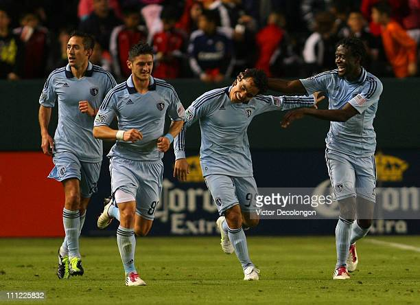 Omar Bravo of Sporting Kansas City is congratulated after his second goal of the game by teammate Kei Kamara as teammate Milos Stojcev jogs upfield...