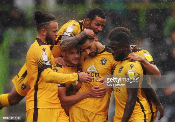Omar Bugiel of Sutton United celebrates with teammates after scoring their team's first goal as Craig Eastmond jumps on top during the Sky Bet League...