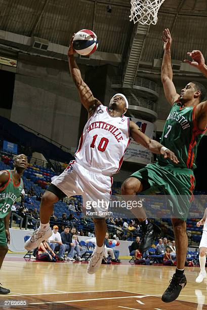 Omar Cook of the Fayetteville Patriots uses the layup against Ime Udoka of the Charleston Lowgators at the Crown Coliseum November 29 2003 in North...
