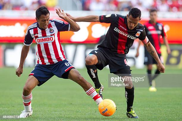 Omar Esparza of Chivas fights for the ball with Leao Ramirez of Morelia during a match between Chivas and Morelia as part of the 13th round of...