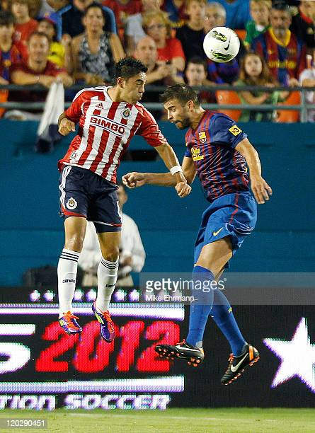 Omar Esperarza of CD Guadalajara goes up for a header against Gerard Pique of FC Barcelona during the 2011 World Football Challenge at Sun Life...