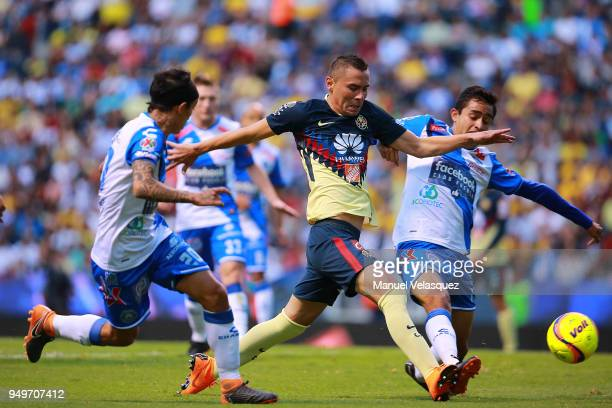 Omar Fernandez and Alonso Zamora of Puebla struggle for the ball with Paul Aguilar of America during the 16th round match between Puebla and America...