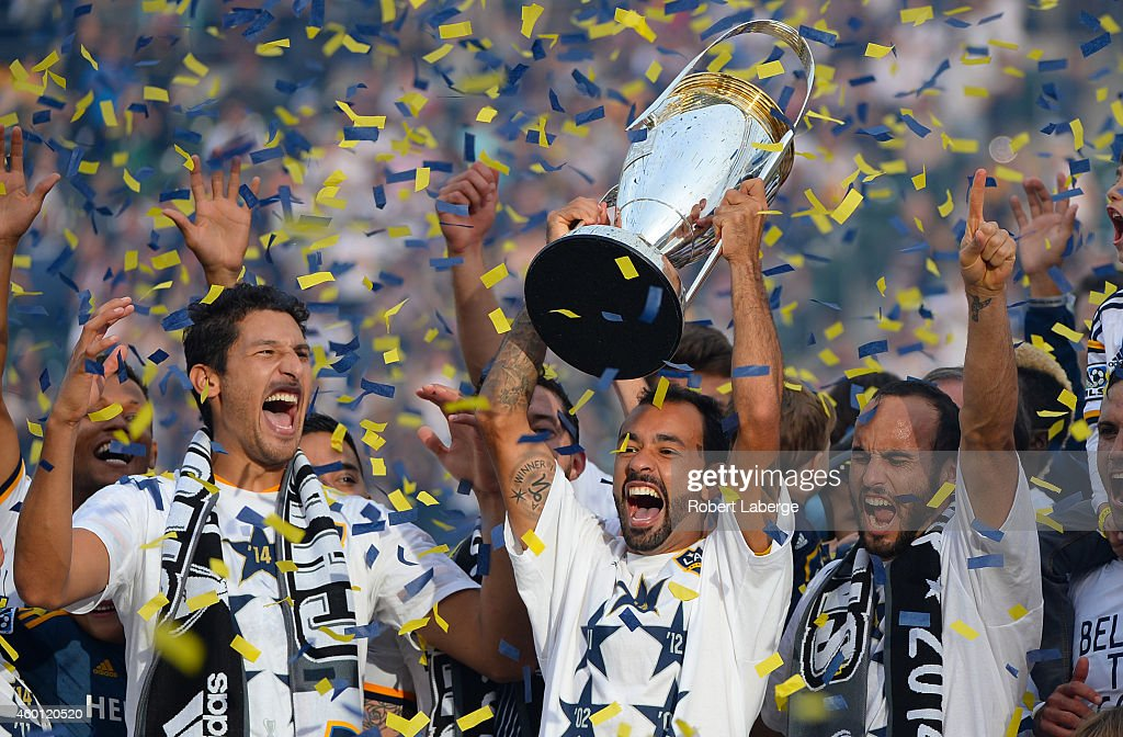 Omar Gonzalez, Juninho and Landon Donovan of the Los Angeles Galaxy celebrate with the Phillip F. Anschutz Trophy after defeating the New England Revolution during the 2014 MLS Cup match at the at StubHub Center on December 7, 2014 in Los Angeles, California.