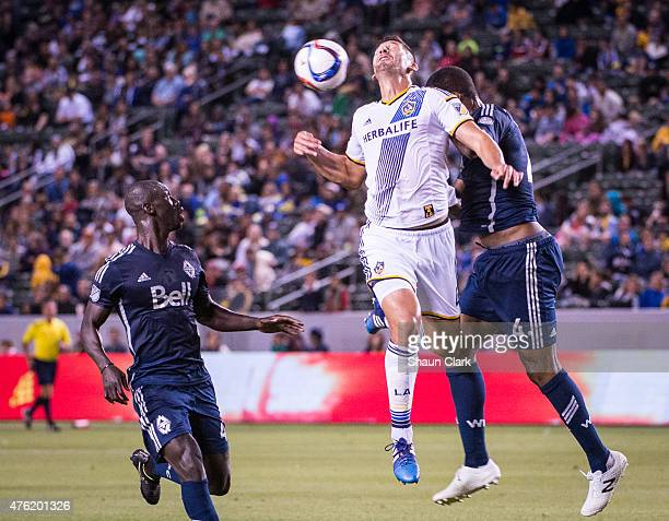 Omar Gonzalez of Los Angeles Galaxy attempts to get on the end of a cross under pressure from Kendall Waston and Pa Modou Kah of Vancouver FC during...