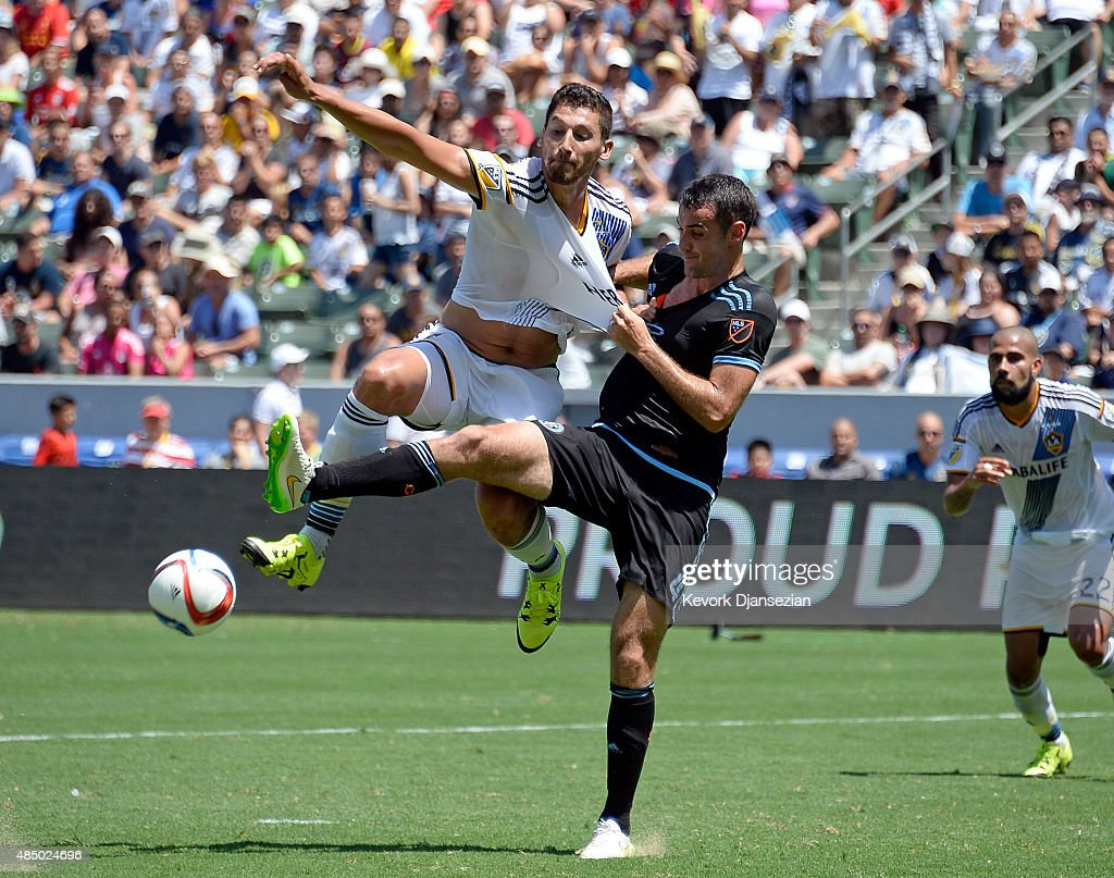 Omar Gonzalez #4 of Los Angeles Galaxy gets his shirt pulled by Andrew Jacobson #4 of New York City FC as reaches for the cross over pass at StubHub Center August 23, 2015, in Carson, California.