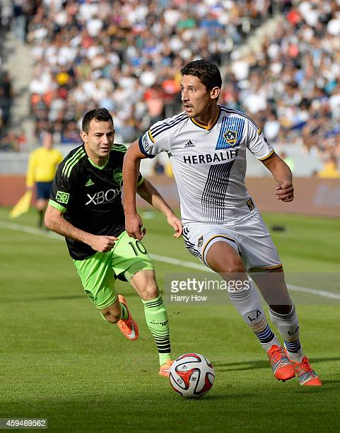 Omar Gonzalez of Los Angeles Galaxy looks to pass as he is chased by Marco Pappa of Seattle Sounders FC during the Western Conference Final at...