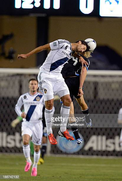 Omar Gonzalez of the Los Angeles Galaxy leaps and hits a header over the back of Steven Lenhart of the San Jose Earthquakes during the first half of...