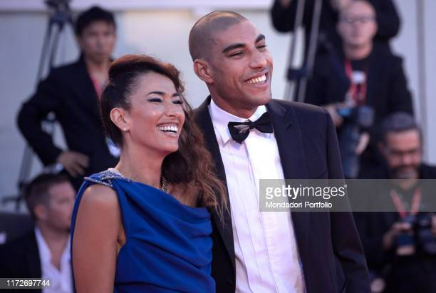 """Omar Hassan and Nina Zilli walk the red carpet ahead of the """"Gloria Mundi"""" screening during the 76th Venice Film Festival at Sala Grande on September..."""