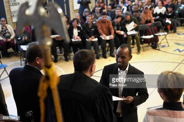 Omar Ibrahim formerly of Somalia in East Africa faces accepts his certificate of citizenship from Immigration Judge Ivan Gardzelewski after taking...