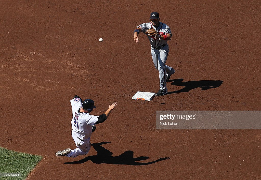 Omar Infante #4 of the Atlanta Braves turns a double play over the slide of Lucas Duda #21 of the New York Mets at Citi Field on September 19, 2010 in the Flushing neighborhood of the Queens borough of New York City.