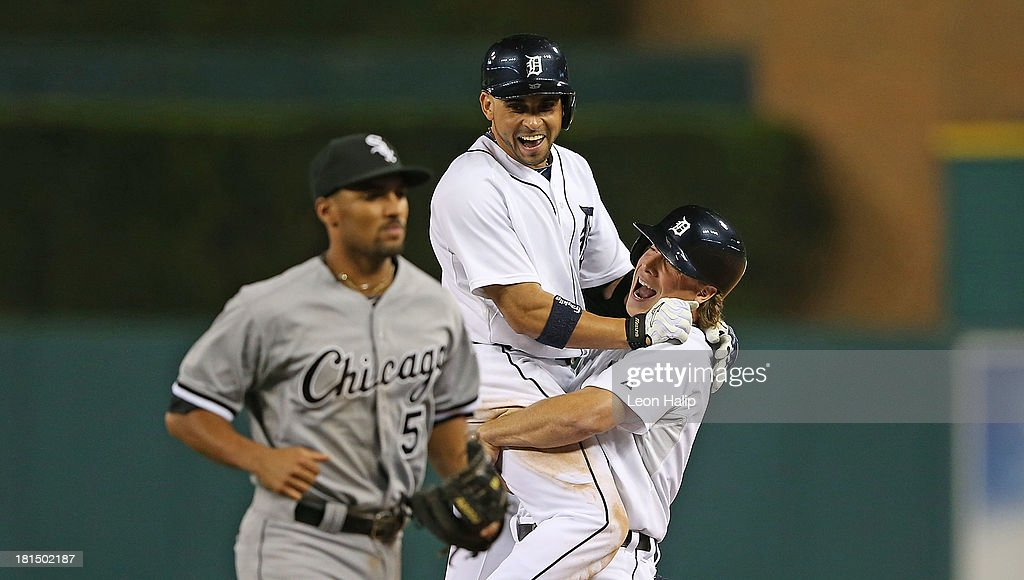 Omar Infante #4 of the Detroit Tigers celebrates with teammate Andy Dirks #12 after hitting an infield single scoring Don Kelly #32 to win the game in the bottom of the 12th inning of the game against the Chicago White Sox at Comerica Park on September 21, 2013 in Detroit, Michigan. The TIgers defeated the White Sox 7-6.