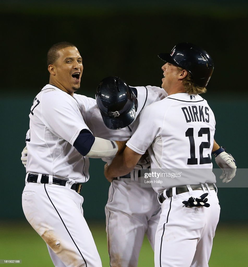 Omar Infante #4 of the Detroit Tigers celebrates with teammates Victor Martinez #41 and Andy Dirks #12 after hitting an infield single scoring Don Kelly #32 to win the game in the bottom of the 12th inning of the game against the Chicago White Sox at Comerica Park on September 21, 2013 in Detroit, Michigan. The TIgers defeated the White Sox 7-6.