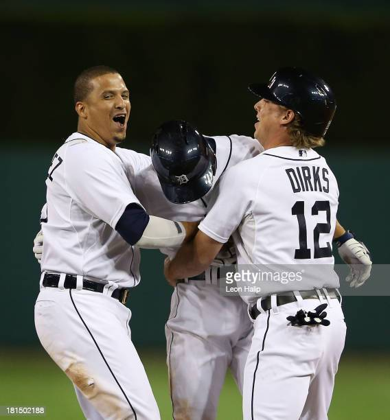 Omar Infante of the Detroit Tigers celebrates with teammates Victor Martinez and Andy Dirks after hitting an infield single scoring Don Kelly to win...