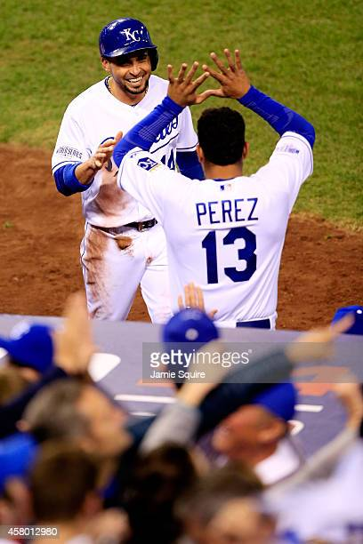 Omar Infante of the Kansas City Royals celebrates with Salvador Perez after scoring in the fifth inning against the San Francisco Giants during Game...