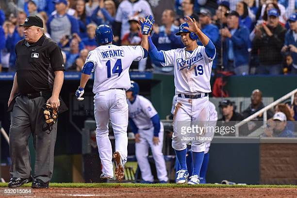 Omar Infante of the Kansas City Royals high-fives teammate Cheslor Cuthbert after scoring the fourth and fifth runs of the game on a Paulo Orlando...