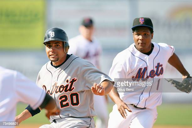 Omar Infante#20 of the Detroit Tigers tries for second as he is trapped by Anderson Hernandez the New York Mets in a spring training game on February...