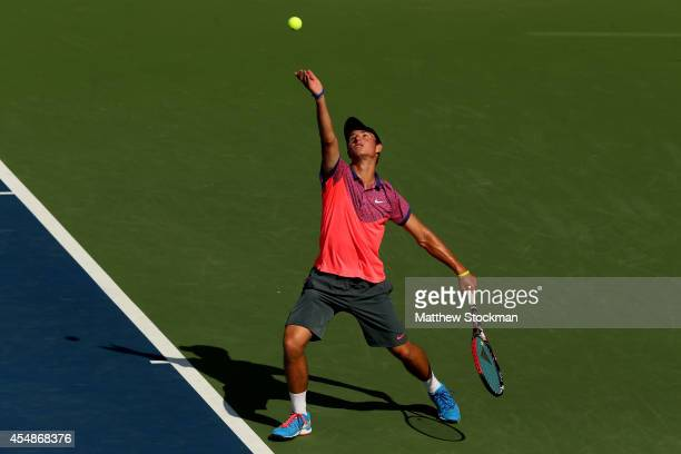 Omar Jasika of Australia serves Quentin Halys of France during their junior boys' singles final match on Day fourteen of the 2014 US Open at the USTA...