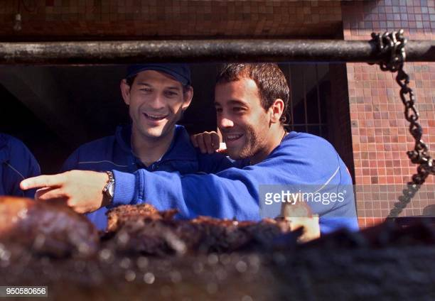 Omar Luis Rodriguez and Jose Saturnino Cardozo of Mexico's Cruz Azul prepare to eat an Argentine barbecue at the Independiente Club in Buenos Aires...