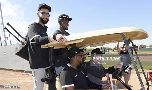 Omar Mazara Eloy Jimenez Luis Robert and third base coach Nick Capra of the Chicago White Sox ride on a golf cart during spring training workouts on...