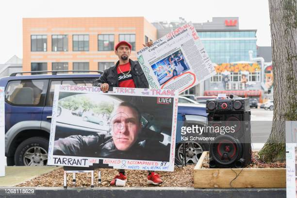 Omar Nabi, whose father Daoud Nabi was killed at Al Noor Mosque, holds conspiracy theory posters in front of Christchurch High Court during the...