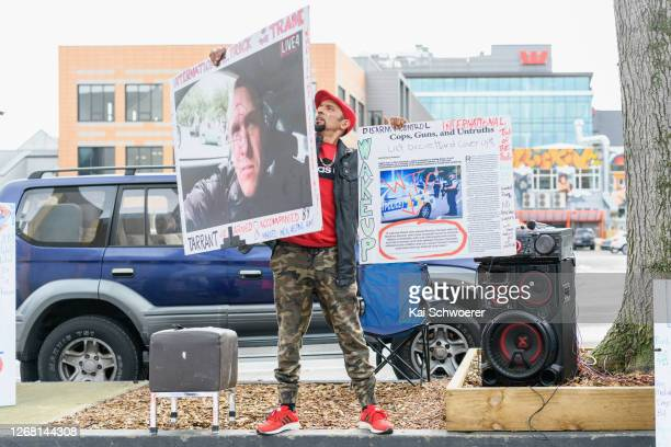 Omar Nabi whose father Daoud Nabi was killed at Al Noor Mosque holds conspiracy theory posters in front of Christchurch High Court during the...
