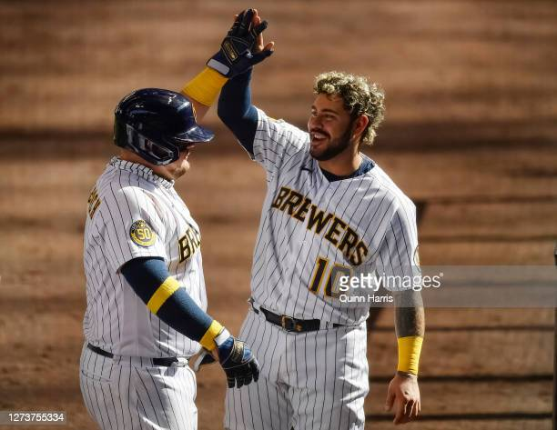 Omar Narvaez of the Milwaukee Brewers congratulates Daniel Vogelbach of the Milwaukee Brewers for his three run home run in the sixth inning against...