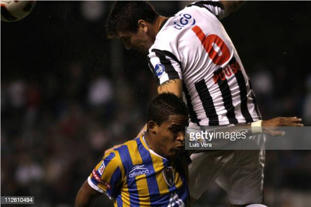 Omar Pouso and of Libertad struggles for the ball with Michael Arroyo of San Luis during a match in the Santander Libertadores 2011 Cup at Nicolas...