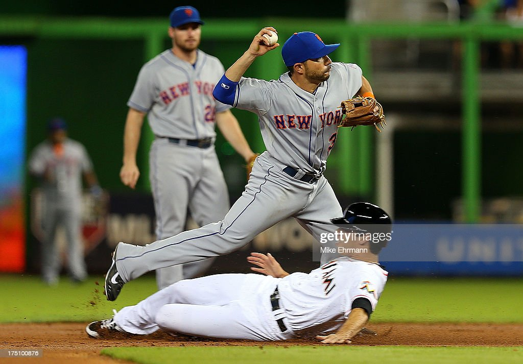 Omar Quintanilla #3 of the New York Mets turns a double play as Jake Marisnick #23 of the Miami Marlins slides into second during a game at Marlins Park on July 31, 2013 in Miami, Florida.