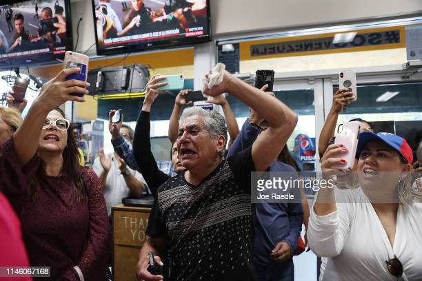 Omar Rojas and others show their support for the interim Venezuelan President Juan Guaido as they watch events unfold in the country on television at...