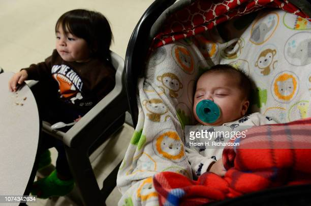 Omar Rojas left and his tiny 2 month old brother Jesus right sit at a table while their mother Kayle Rojas not shown gets prepared to feed them...
