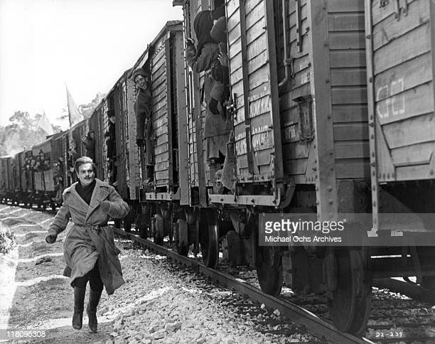 Omar Sharif races past cheering passengers to board train where his family awaits him in a scene from the film 'Doctor Zhivago' 1965