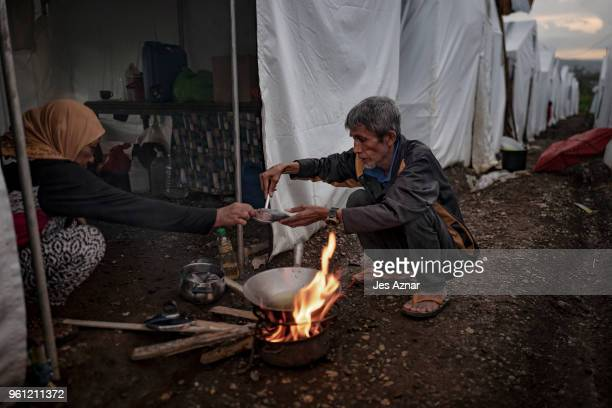 Omar Shariff and his wife Potre Soltan Macalatas cooks fish as they prepare their last meal before fasting for Ramadan inside the Sarimanok tent city...