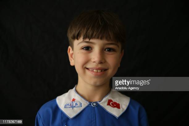 Omar Zuhal, a nine year-old Syrian boy from Hama, poses for a photo with a school uniform in Reyhanli district of Turkey's southern Hatay province on...